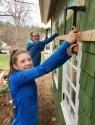Girls Hammering up Cedar Siding